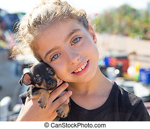 kid girl playing with puppy dog smiling with blue eyes