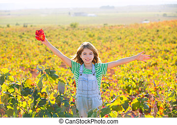Kid girl in happy autumn vineyard field open arms with red leaf