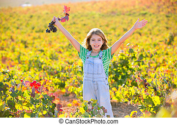 Kid girl in happy autumn vineyard field open arms with red leaf grapes bunch in hand