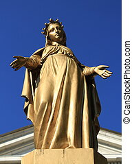 Virgin Mary statue - Golden virgin Mary statue in front of a