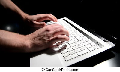 Hands typing text on a laptop