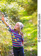 kid winter girl picking mulberry berries in the forest with...
