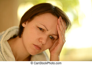 Sick woman with headache holding her head with hands
