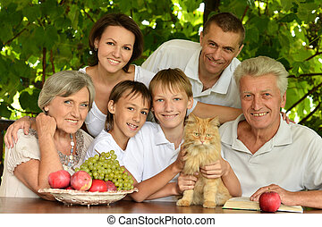 Happy parents and children at a table eating fruits in...