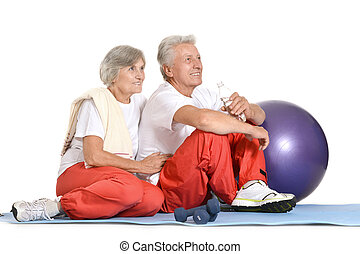 Fit senior couple - Elderly couple exercising on a floor of...