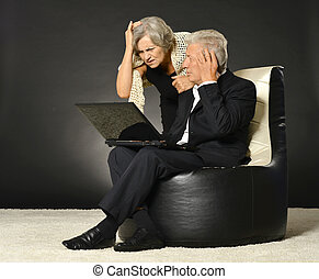 Elderly couple using laptop - Senior couple working with...