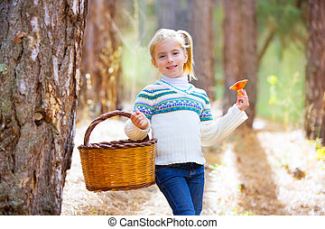 kid girl searching chanterelles mushrooms with basket in...