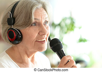 Senior woman singing into microphone