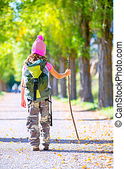 hiking kid girl with walking stick and backpack rear view at...