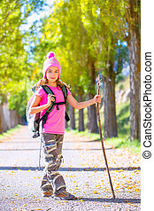 hiking kid girl with walking stick and backpack in autumn -...