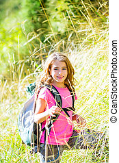 Explorer kid girl walking with backpack in grass - Explorer...