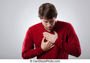 Angina - Young man with strong lungs ache holding his chest