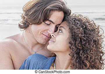 Young happy couple together at beach - Young Caucasian man...