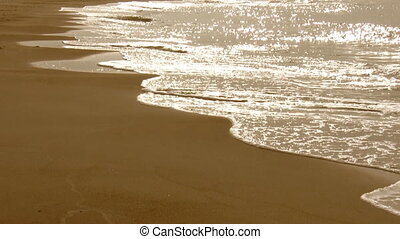 Waves breaking on the beach - Sea waves splashing on a sandy...