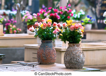 two vases of flowers on a tombstone in a cemetery