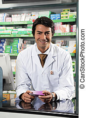 pharmacy - portrait of mid adult pharmacist looking at...