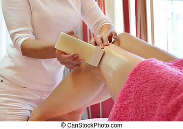day at the beauty salon - woman having her legs waxed in spa...
