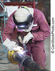 Craftman in a safety suit is welding a metal pipe -...