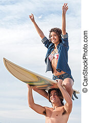 Surfer couple - Young Caucasian surfer guy holds board on...