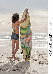 Surfer girl - Beautiful young surfer girl standing with...