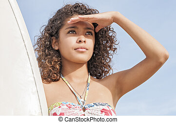 Surfer girl - Beautiful young surfer girl shields eyes from...