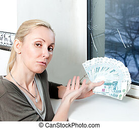 The sad young woman counts money for window repair with the burst, broken glass