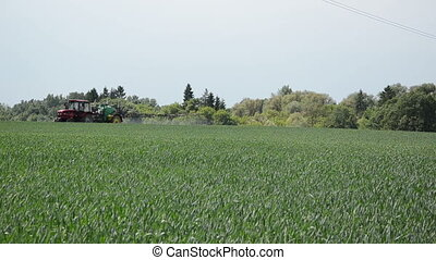 green field tractor - a farm old tractor fertilizes a green...