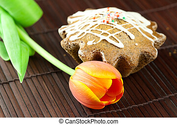 cake with icing and a tulip lying on a bamboo mat
