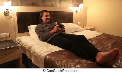 hotel room - attractive man playing smart phone in hotel...