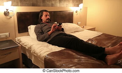 hotel room - attractive man using smart phone in hotel room