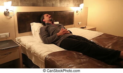 hotel room - attractive man resting on the bed in hotel room...
