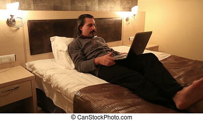 hotel room - attractive man using laptop in hotel room