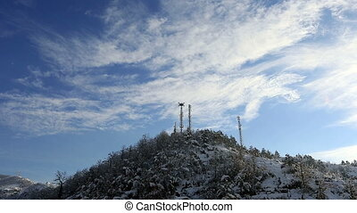 winter scenes - time lapse telecommunication tower and pine...