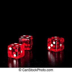 three red dice on old wood black table with space for text -...