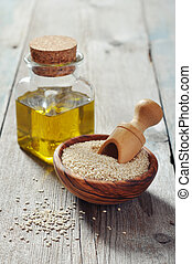 Sesame seeds and oil in bottle on wooden background