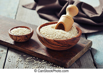Sesame seeds in wooden bowl on wooden background