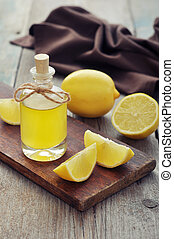 Lemon oil in a glass bottle with fresh lemon on wooden...