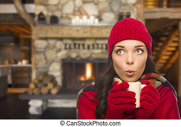 Mixed Race Girl Enjoying Warm Fireplace and Holding Mug -...