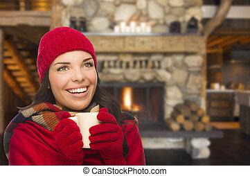 Mixed Race Girl Enjoying Warm Fireplace and Holding Mug -...