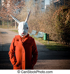rabbit mask woman red coat winter desolate landscape