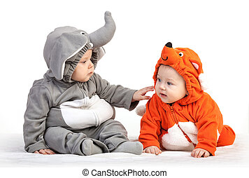 Two baby boys dressed in animal costumes playing over white...