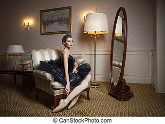 Ballerina in black tutu sitting in armchair in luxury...