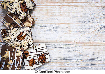 Chocolate bark on wood background - Assorted chocolate...