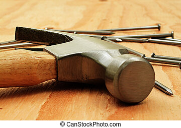 Hammer And Nails On Plywood - A steel hammer with a wooden...