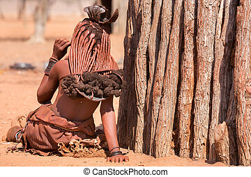 Himba woman - Rear view of himba woman outside shack