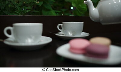 Tea with macaroons in cafe. - In cafe: pouring tea into two...