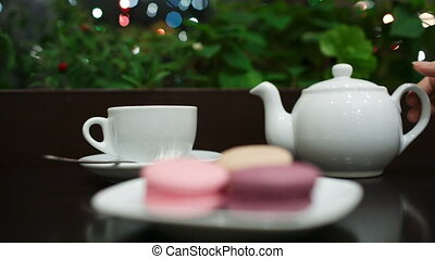 Tea with macaroons in cafe - In cafe: pouring tea into white...