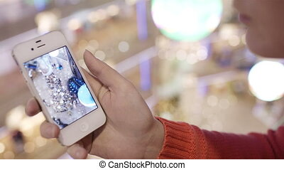 Using smartphone. - Woman looking through the photos of...