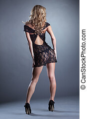 Slender curly blonde posing in black lace negligee back to...