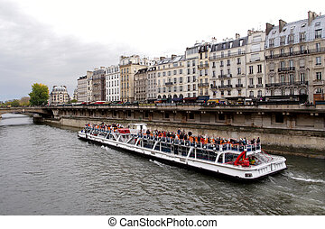rowing by seine - boat with tourists rowing by the Seine...